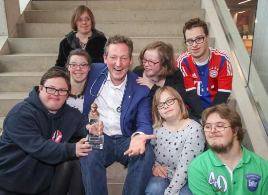 Dr. Eckart von Hirschhausen,  umrahmt von den Down-Syndrom-Ehrengästen